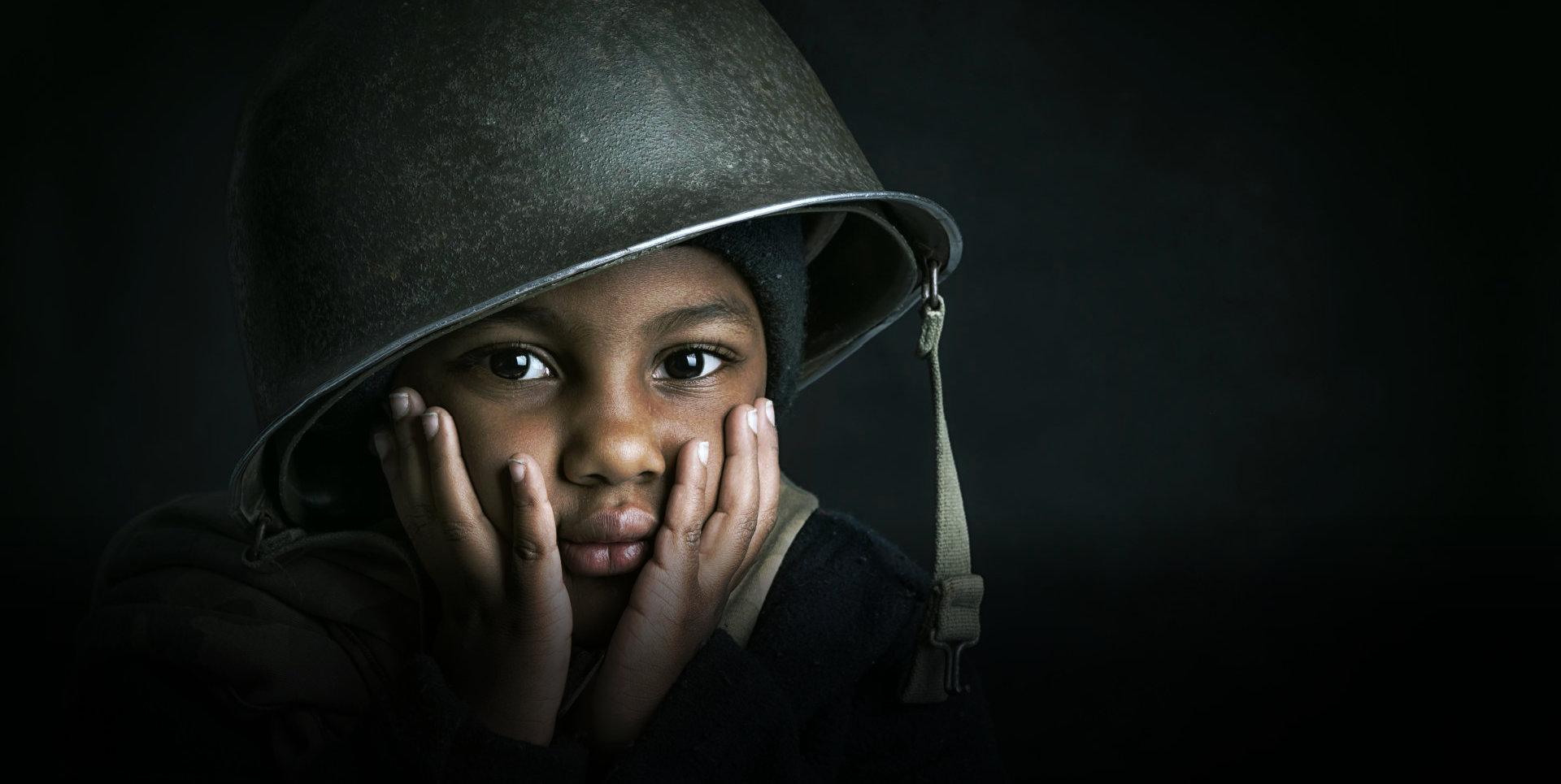 kid wearing a solider's helmet