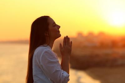 a portrait of a woman praying